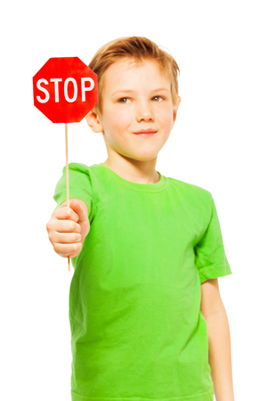Close-up portrait of young fair-haired boy in green tee, holding small red Stop sign, isolated on white Stock Photo