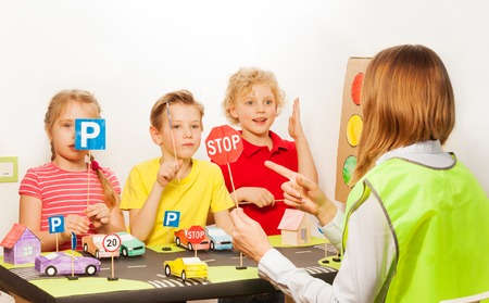 Weibliche Lehrer in Warnweste eine Klasse von Straßenverkehrssicherheit für Kinder und deutet auf ein Stop-Schild in den Kindergarten Unterricht Standard-Bild