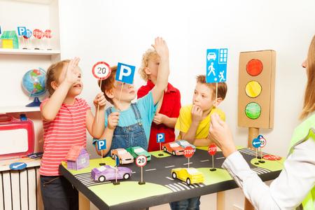 Vrouwelijke leraar die Thuiszone teken aan haar weinig leerlingen op de verkeersveiligheid les in de kleuterschool Stockfoto
