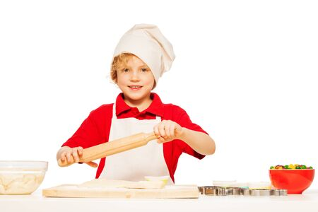rolling: Young baker, kid boy in apron and toque, making dough with rolling pin, isolated on white Stock Photo