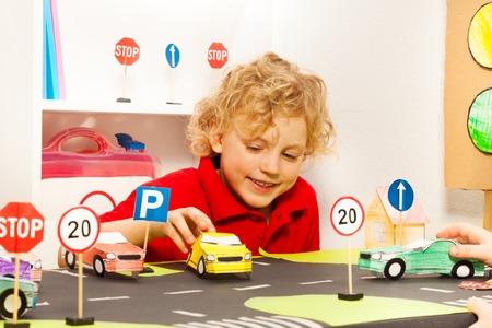 paso de peatones: Muchacho sonriente cinco años jugando conductor con coches de juguete de papel en la clase de seguridad vial