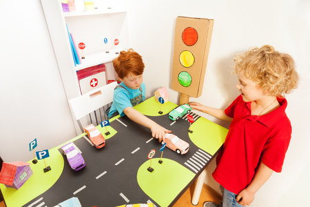 road safety: Top view of two boys, happy friends, playing drivers with their toy cars in the road safety class