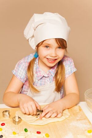pastry cutters: Cute young baker, girl in white apron and toque, cutting off the dough for candy filled cookies Stock Photo