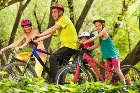 Sports family, mother, father and two age-diverse daughters, having fun cycling in the spring forest Stock Photo