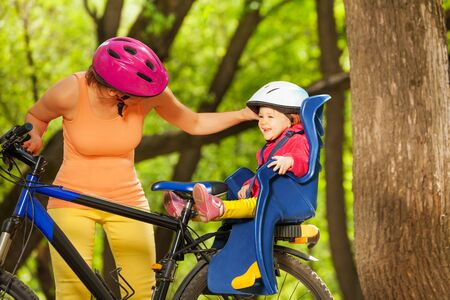 enfant banc: Smiling toddler girl in bicycle child seat and protection helmet smiling and mother talking to daughter Banque d'images