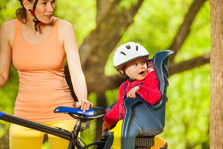 Portrait of amazed toddler girl with protection helmet on her head, sitting in bike seat, cycling with her mom
