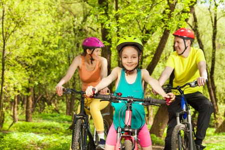 Happy teenage girl in helmet having fun the cycling at the spring park with her parents Stockfoto