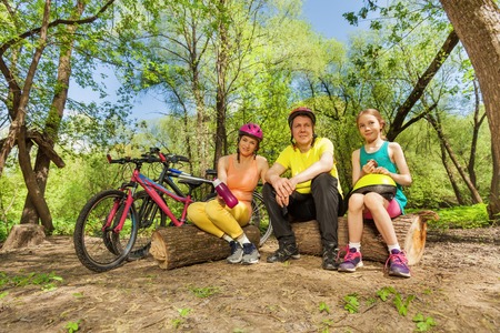 active family: Active family resting and making pause on a log in the sunny spring wood, tired after cycling