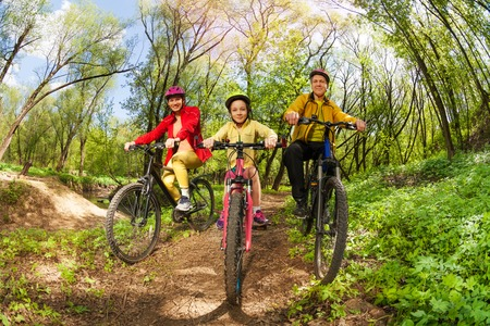 Happy active family, mother, father and girl, mountain biking on forest trail at the sunny day Archivio Fotografico
