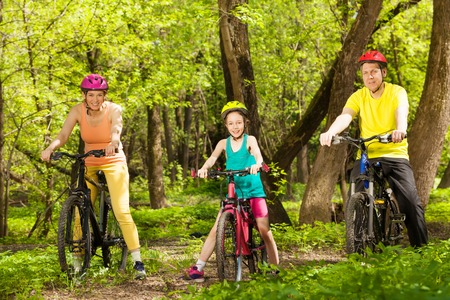 Picture of sports family, mother, father and teenage girl cycling in the sunny spring forest