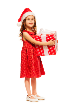six years: Nice little six years old girl standing with big red box present with white ribbon bow wearing Santa hat