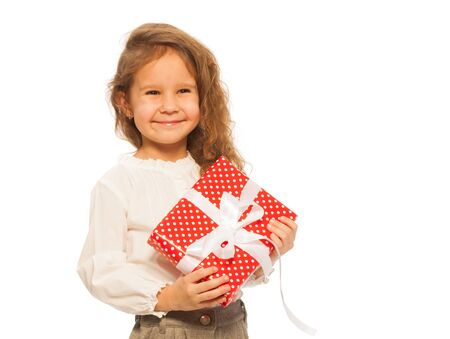 5 year old girl: Cute little girl with small red present and happy face standing isolated on white Stock Photo