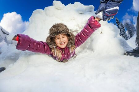 Kids are pulling smiling girl from big snow cave