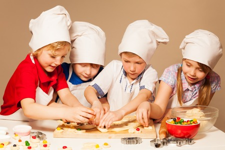 Four cute bakers, boys and girl in cooks uniform having fun making candy filled cookies