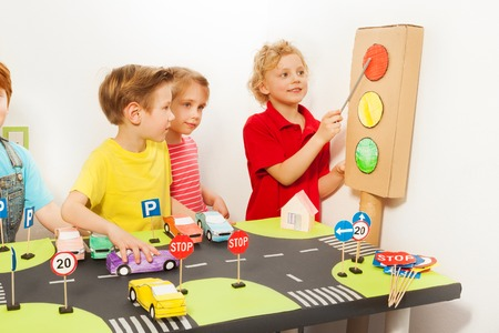 traffic rules: Smiling friends playing drivers with handmade cardboard light-signal, toy cars and road signs at the road playing field Stock Photo