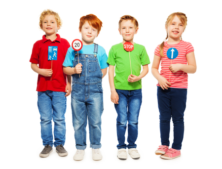 Group of four kids, boys and girl standing in a row, holding small models of road signs, isolated on white