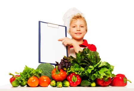 blanked: Kid boy in cooks uniform holding blanked clipboard menu, standing behind the table full of fresh vegetables, isolated on white