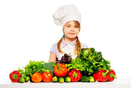 toque: Young cook, girl in white apron and toque standing with fresh vegetables, isolated on white