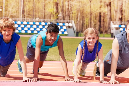 Happy multiethnic teenagers in sportswear doing push-up exercises while standing on the track on stadium