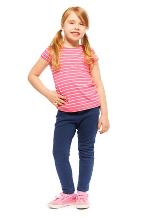 Full-length picture of beautiful seven years old girl in tee and leggings, posing at the camera, isolated on white Stock Photo