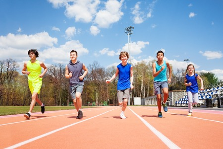 Portrait of five teenage sprinters, running together on the racetrack in spring