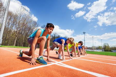 Zijaanzicht van vijf tieners atleten, klaar om op de baan te lopen, op een rij staan