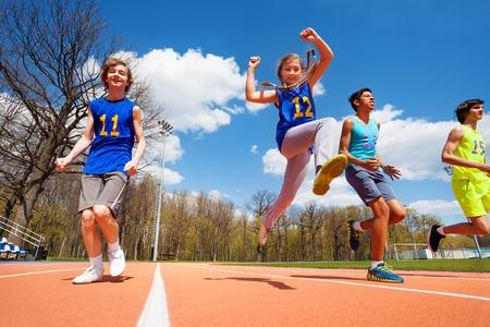 Vier gelukkige tiener atleten lopen op het stadion, onderaanzicht