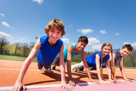 Close-up foto van vier gelukkige tieners in sportkleding met een plank staan in een rij op de baan buitenshuis Stockfoto