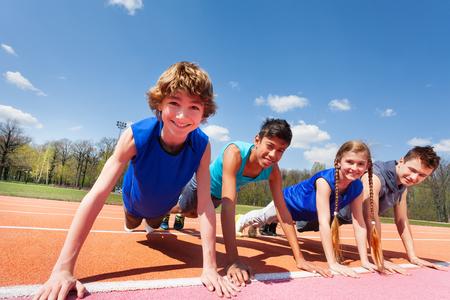 Foto de primer plano de cuatro adolescentes felices en ropa deportiva sosteniendo un tablón de pie en una fila en la pista al aire libre Foto de archivo