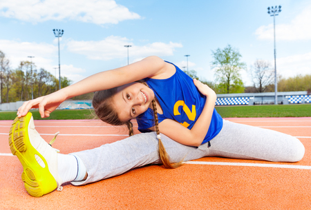 Happy teenage girl in sportswear making yoga stretching on the stadium on sunny day Archivio Fotografico