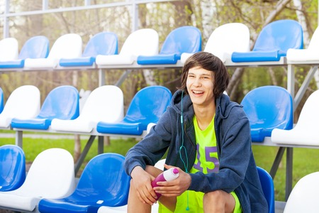 tribune: Happy smiling teenage athlete having rest after workout, sitting at the tribune