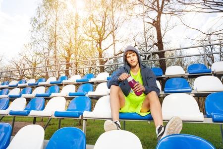 atletismo: atleta adolescente tener descanso después de hacer ejercicio, sentado en la tribuna con la botella de agua Foto de archivo