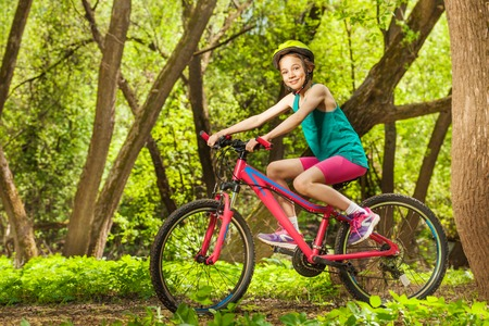 Side view picture of smiling young girl in bicycle helmet, cycling through spring park Stock Photo
