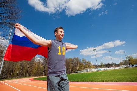 racetrack: Happy teenage sprinter, boy in sportswear, waving flag of Russian Federation, running on the racetrack Stock Photo