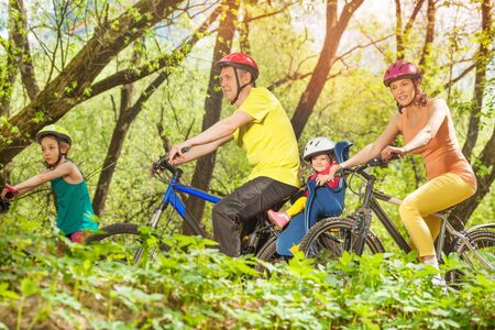 Sporty family running bikes in the sunny spring forest