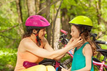 Sporty mother helping her young daughter to clasp bicycle helmet before cycling Stock Photo