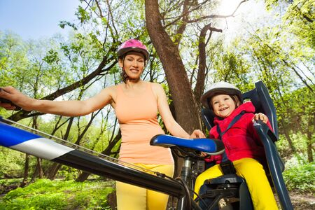 helmet seat: Little toddler girl in bicycle helmet sitting in  bike seat outdoors with her sporty mother