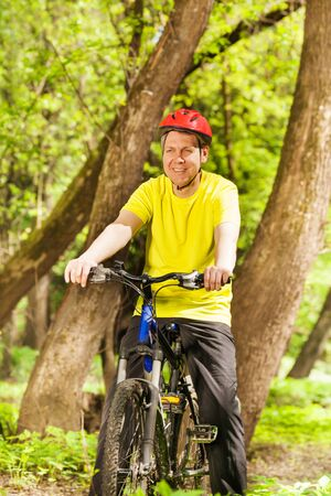 Portrait of active man in bicycle helmet riding his mountain bike on forest trail