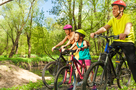 Happy cyclists, father, mother and girl, admiring the landscape of sunny spring wood riding their bikes