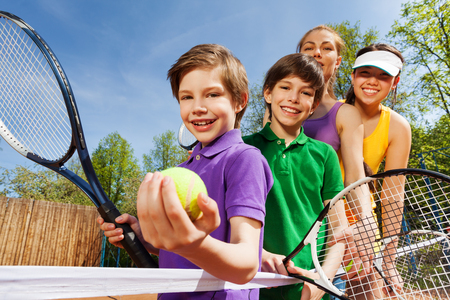 Close-up portrait of smiling active family, holding tennis rackets and ball on the court in sunny day Stockfoto