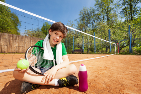 Kid boy having rest after playing tennis, sitting on the clay court near the tennis net, holding racket and ball Stock Photo