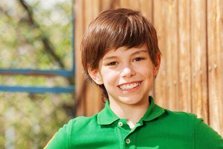 Close-up portret uśmiechnięta dziesięć lat chłopiec w zielonej koszulce polo