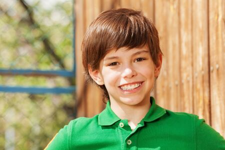 Close-up portret van lachende tien jaar oude jongen in groen polo shirt