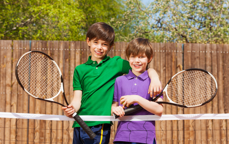 young boys: Portrait of two happy friends, young boys, standing together next to the net after tennis match
