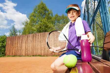 player bench: Portrait of tennis player, young boy with water bottle, having rest sitting on the bench after tennis game