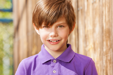 Close-up portrét deseti let bruneta chlapce ve fialové polokošile, venku v létě