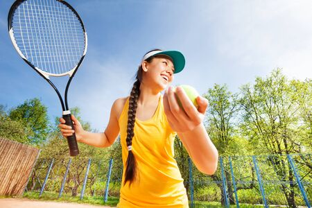 Sporty teenage girl with tennis ball and racket preparing to serve on the court in summer