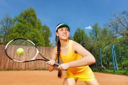 girl action: Professional tennis player, determined young girl in action on the clay court in summer Stock Photo