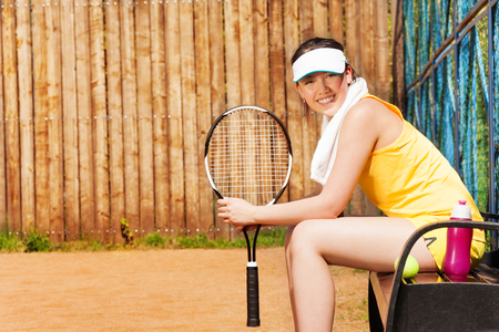 player bench: Side view of smiling teenage girl, tennis player, sitting on the bench after the game on the clay court