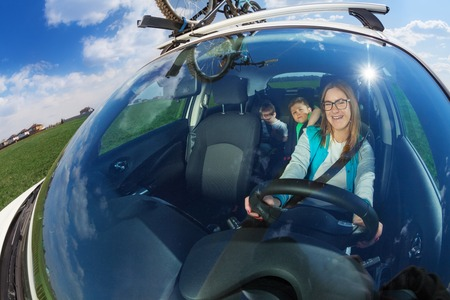 wide angle lens: Happy female driver travelling by car with two kid boys on sunny day, view through a windscreen, shot with wide angle lens Stock Photo